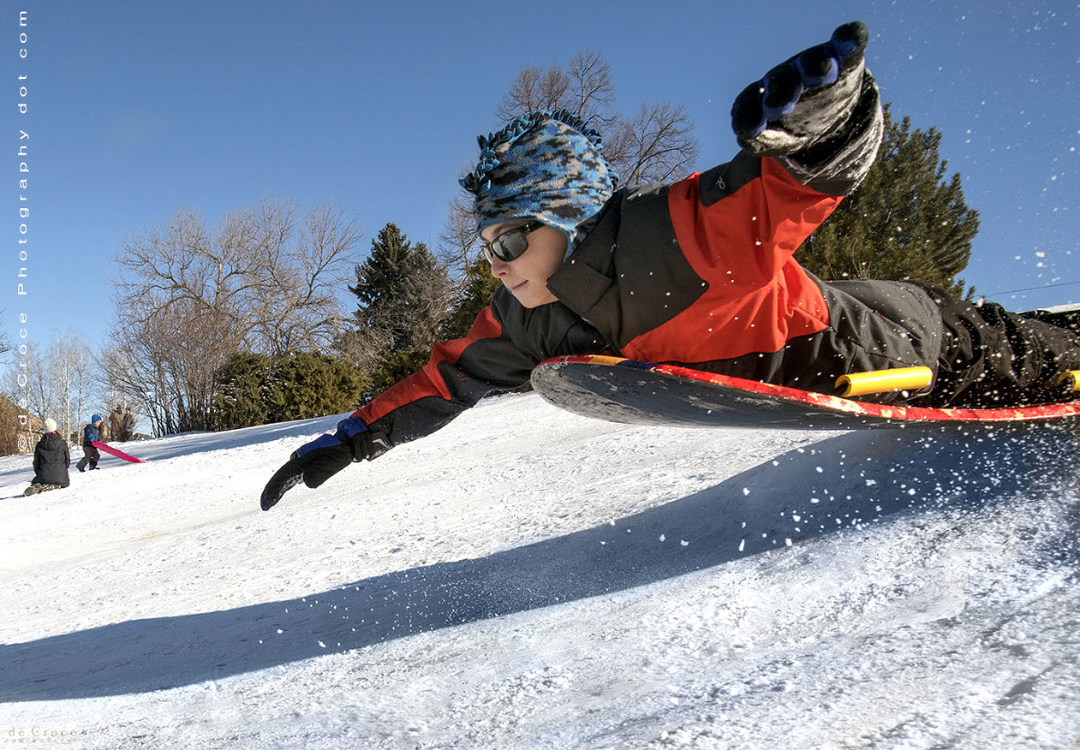 boy sledding in winter